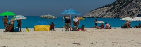 Ludzie cieszą się słońce na plaży, Myrtos plażowy Kefalonia Grecja obraz stock
