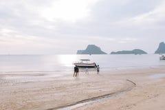 Ludzie czekają i oglądają na brzeg jako łodzie rybackie na morzu Zdjęcia Royalty Free