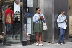 Ludzie czekają przyjaciół blisko Covent ogródu, zakopujących w telefonach komórkowych Fotografia Stock