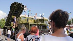 Ludzie fotografują na telefonie komórkowym blisko wielkiego militarnego samochodu w na wolnym powietrzu zdjęcie wideo