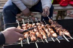 Ludzie gotują mięso na grillu Obrazy Royalty Free