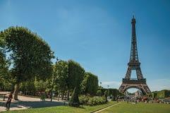 Ludzie, greenery i wieża eifla z pogodnym niebieskim niebem w Paryż, Fotografia Stock