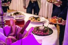 Ludzie grupują cateringu bufet przy jedzenie stołu luksusową restauracją z mięsa, chlebowej i różnej sałatką, obrazy royalty free
