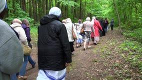 Ludzie iść z księżmi i michaelita z krzyżem przecinający sposób 4K zbiory