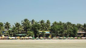 Ludzie i plaż loungers pod pogodnymi kolorowymi parasolami na piasku przeciw tłu bary i restauracje w zieleni p zbiory