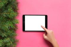 Ludzie i technologii pojęcie, zakończenie w górę żeńskich ręk wskazuje palec pastylka pusty ekran na różowym tle, odgórny widok zdjęcie stock