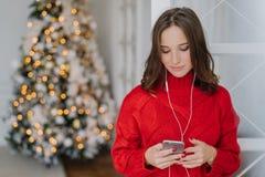 Ludzie i wakacje pojęcie Skoncentrowana ciemna z włosami młoda kobieta trzyma telefon komórkowego w rękach, czyta wiadomość w int zdjęcie royalty free