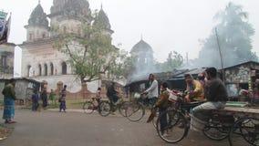 Ludzie jadą bicykle ulicą na zimnym mgłowym ranku w Puthia, Bangladesz zbiory