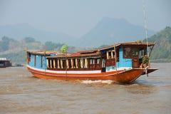 Ludzie jadą tradycyjną długą łódź Mekong rzeką w Luang Prabang, Laos Obrazy Royalty Free