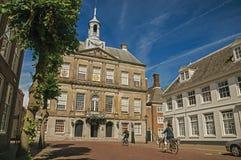 Ludzie jechać na rowerze na ulicie przed urzędu miasta budynkiem na słonecznym dniu w Weesp Zdjęcie Stock