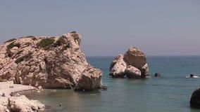 Ludzie kąpać i sunbathe na małej piaskowatej plaży miejsce narodzin Aphrodite na wyspie Cypr, skały wtykają out zbiory wideo