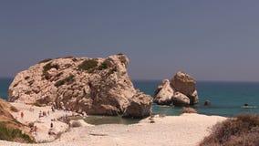 Ludzie kąpać i sunbathe na małej piaskowatej plaży miejsce narodzin Aphrodite na wyspie Cypr, skały wtykają out zbiory