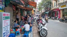 Ludzie konserwują widzią mieć ich jedzenie obok ulicy w ranku przy Hanoi, Wietnam Obrazy Stock