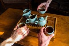 3 ludzie kosztuje ciemnej oolong herbaty i pije w małe smaczne filiżanki obraz royalty free