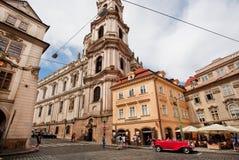 Ludzie krzyżuje brukowiec drogę z retro samochodem i dziejowych domy Praga Obraz Stock