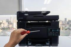Ludzie lewa ręka chwyta czerwonych śrubokrętów dla naprawy i utrzymania drukarki Zdjęcie Stock