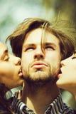 Ludzie, mężczyzna dostaje buziaka dwa uroczymi dziewczynami fotografia royalty free