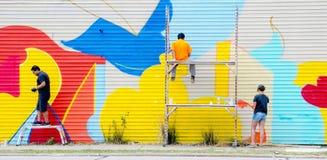 Ludzie maluje graffiti na przemysłowej ścianie Obrazy Royalty Free
