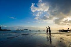 Ludzie na Ao Nang wyrzucać na brzeg przy zmierzchem Zdjęcie Stock