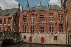 Ludzie na bridżowych i starych budynkach przy kanałem w Bruges Obraz Royalty Free