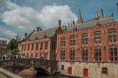 Ludzie na bridżowych i starych budynkach przy kanałem w Bruges Zdjęcie Stock