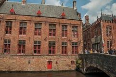 Ludzie na bridżowych i starych budynkach przy kanałem w Bruges Fotografia Royalty Free