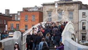Ludzie na brzęczenia ` centu moscie nad Rzecznym Liffey w Dublin, Irlandia zdjęcia royalty free