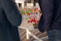 Ludzie na cateringu usługują tło przekąski i kolorowi napoje na stole obraz royalty free