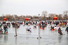 Ludzie na jeziornych mrozie cieszyć się sledding, lodowa łyżwa, lodowy rower przy lato pałac w Pekin w zimie fotografia stock