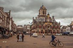 Ludzie na Targowym kwadracie i dekorującym Gockim urzędu miasta budynku na chmurnym dniu w Delft Obraz Stock