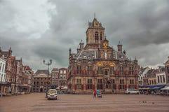 Ludzie na Targowym kwadracie i dekorującym Gockim urzędu miasta budynku na chmurnym dniu w Delft Zdjęcia Royalty Free