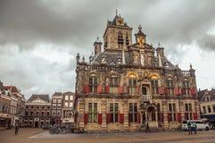 Ludzie na Targowym kwadracie i dekorującym Gockim urzędu miasta budynku na chmurnym dniu w Delft Fotografia Royalty Free