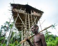 Ludzie od Korowai plemienia blisko swój tradycyjnego domu Plemię Korowai Kombai Zdjęcie Royalty Free
