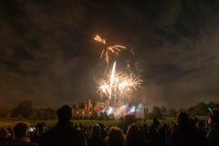 Ludzie ogląda fajerwerku pokazu przy ogniskiem 4th Listopadu świętowanie, Kenilworth kasztel, zlany królestwo Fotografia Stock