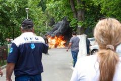 Ludzie ogląda samochód który łapał ogienia w Bucharest, Rumunia Obrazy Stock