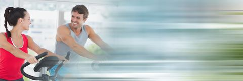 Ludzie ono uśmiecha się na gym jechać na rowerze z rozmytą ruch plamą Fotografia Stock