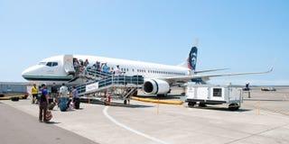Ludzie opuszcza Boeing Alaska Airlines w Koniec przy Keahole interną obraz royalty free