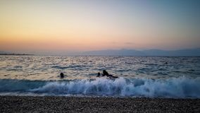 ludzie pływa przy zmierzch plażą obrazy stock