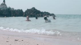 Ludzie pływają w machać bezbrzeżnego ocean przeciw brąz skale zdjęcie wideo
