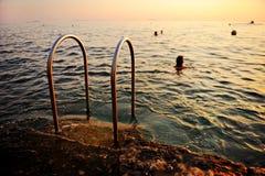 Ludzie pływa w Adriatyckim morzu przy zmierzchem Fotografia Stock