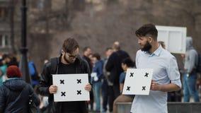 Ludzie patrzeją each inny przy sztandarami przy pozazdroszczeniem i wiecem Dwa faceta na strajku