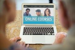Ludzie patrzeje komputer z nauczanie online informacją w ekranie zdjęcia stock