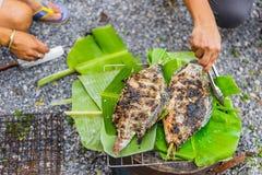 Ludzie Piec na grillu świeżej ryby z solą na węgla drzewnego i banana liściu obraz royalty free