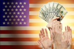 Ludzie podnosi ręki z dolarami i flagę amerykańską na tle Patriotyczny pojęcie zdjęcia stock