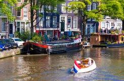 Ludzie podróżują łodzią wzdłuż kanałów Amsterdam przy lato czasem Fotografia Royalty Free