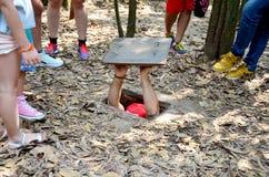 Ludzie podróżują i próbujący bawić się wchodzić do tunel przy Cu Chi Tunne fotografia royalty free