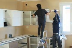 Ludzie pracowników próbuje instalować kuchnię Zdjęcia Stock