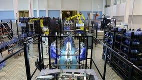 Ludzie pracuje przy magazynem czysta woda butelkowa z robotów ładowaczami zbiory