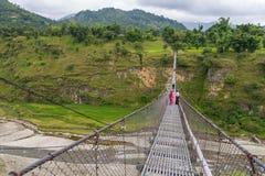 Ludzie przechodzi przez wiszącego mosta nad rzeką Obraz Stock