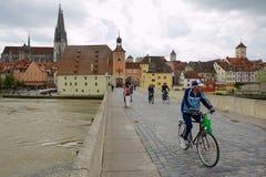 Ludzie przejażdżka bicykli/lów drylują most w Regensbusg, Niemcy Fotografia Stock